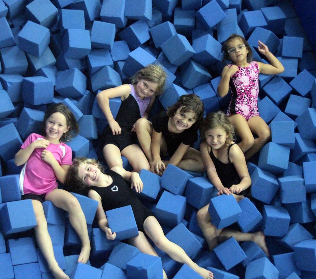 Kids lay smiling in a pile of foam blocks.