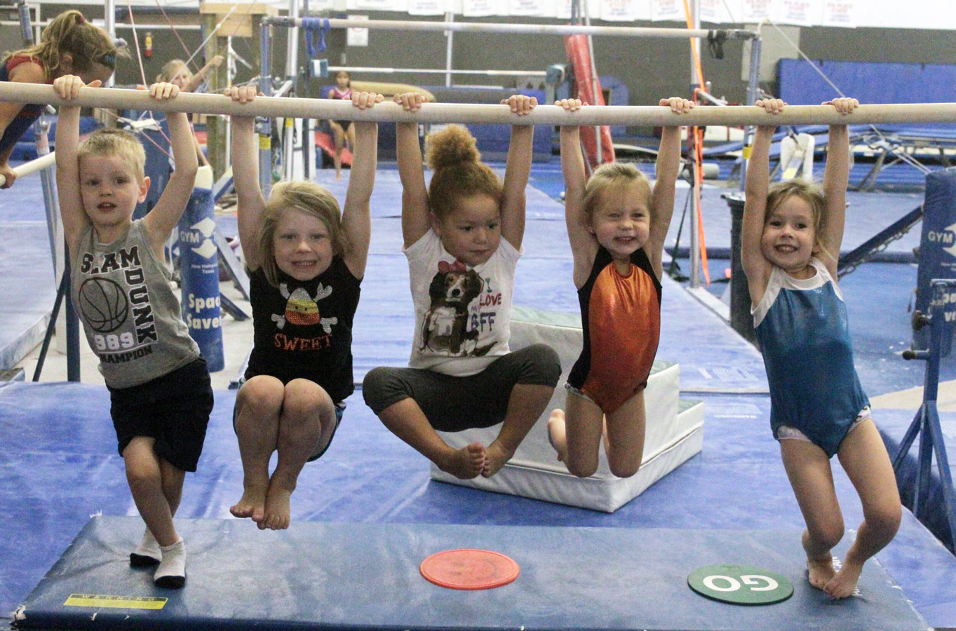 Kids hang from a gym bar.