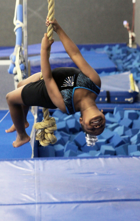 A child swings on a rope over a foam pit.